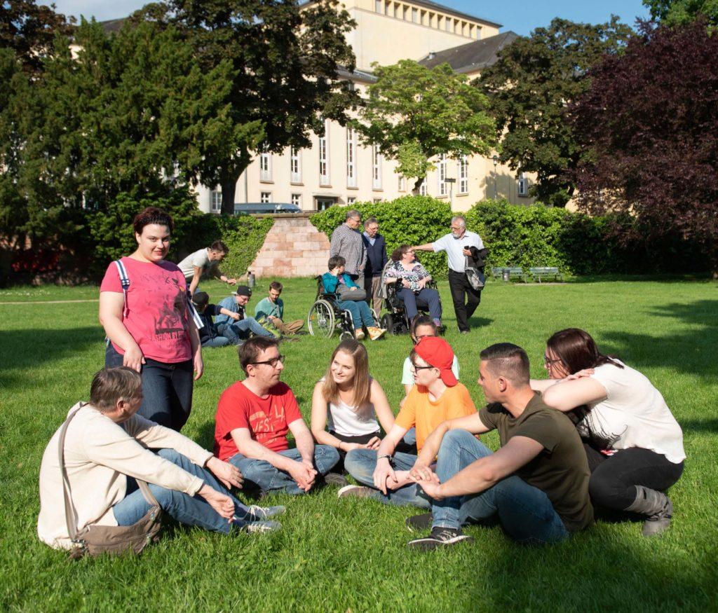 Personengruppe auf Wiese vor dem saarländischen Staatstheater